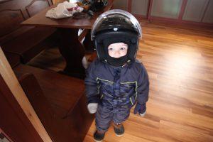 little boy wearing helmet and snow gear