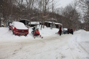 a truck in the snow and snowmobiles