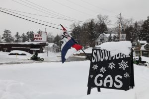 sign for a gas station with OPEN flag