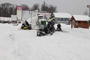 snowmobiles fueling up at temporary fuel station