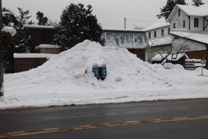 two phone booths submerged in a snow bank