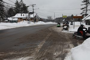 snowmobiles riding down the road
