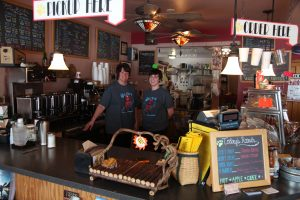 two baristas behind the counter wearing shirts supporting local olympians