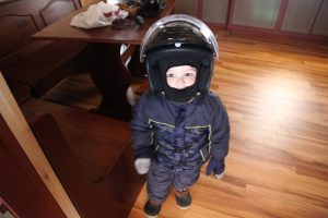 little boy wearing helmet and snow gear