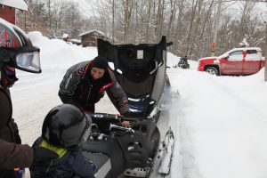 snowmobile with hood open, adding oil