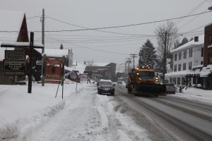 a view of the main street with a plow removing snow